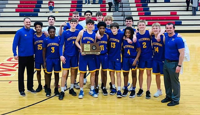 The Hutchinson High School boys basketball team hold their Class 6A Sub-State Championship trophy after defeating Dodge City 67-43 Friday.