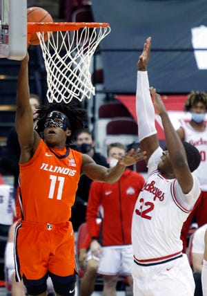 Illinois guard Ayo Dosunmu, left, goes up to shoot against Ohio State forward E.J. Liddell during the first half of an NCAA college basketball game in Columbus, Ohio, Saturday, March 6, 2021.