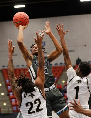 Western's Matthew Robinson Jr. (1) and Julian Lewis (22) defend as Dwyer's Kyle McNeal elevates to shoot over them in the first quarter of their Class 7A semifinal game on Friday afternoon in Lakeland.
