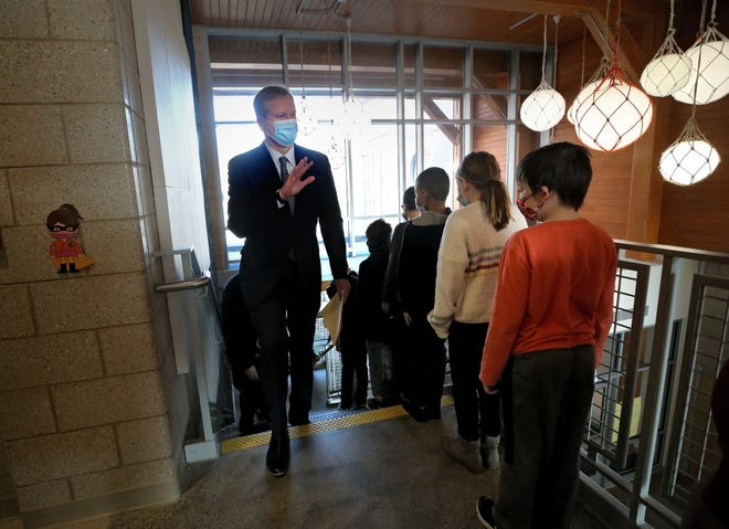 Gov. Charlie Baker waves to a line of students Wednesday during a visit to Gloucester's West Parish School, where pupils have been learning in person for more than 100 days.