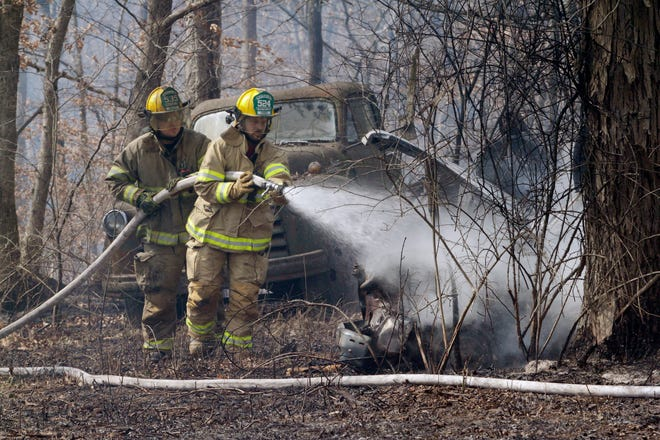 Two volunteer firefighters with the Westran Fire Protection District water down an old non-operable vehicle Saturday morning on the grounds of a natural cover fire on property located in southwest Moberly at 1672 County Road 2275.