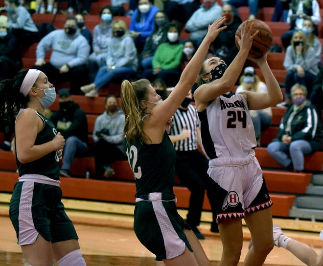 New Boston Huron's Alexis Thomas goes to the hoop on a fast break past Audrey Cousino and Caroline Roecker of SMCC Saturday. Huron won 40-34.