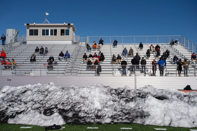 A small number of Wayland fans are socially distanced in the stands during a pre-season football scrimmage in Wayland against Waltham High on March 6, 2021.