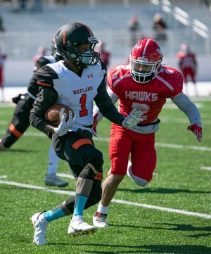 Wayland senior Jaison Tucker carries the ball up the field, as Waltham senior Joshua Lopez closes in, during a pre-season scrimmage in Wayland, March 6, 2021. Tucker rushed for 182 yards and four touchdowns in the Warriors' season-opening win over Boston Latin Friday night.