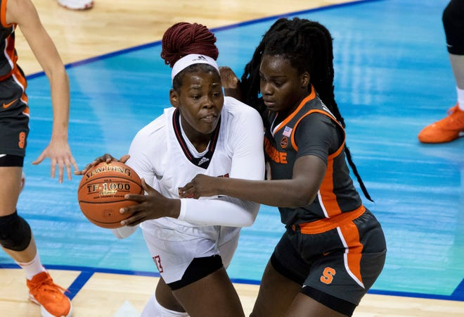 Louisville's Olivia Cochran, left, handles the ball in the post against Syracuse's Maeva Djaldi-Tabdi during the first half of a semifinal game in Atlantic Coast Conference tournament Saturday in Greensboro, N.C.