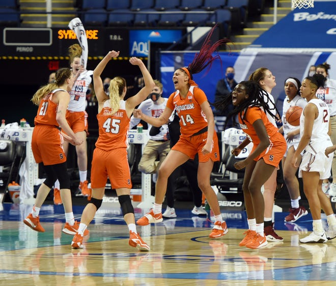Syracuse players mob Kamilla Cardoso (14) after she hit the game-winning shot at the buzzer to beat Florida State in the quarterfinals of the Atlantic Coast Conference tournament, Friday at the Greensboro Coliseum in Greensboro, N.C.