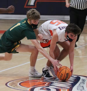 Pontiac's Michael Kuska, right, battles with Blake Staab of Champaign (St. Thomas More) to maintain possession of the ball during Friday's basketball contest at PTHS.