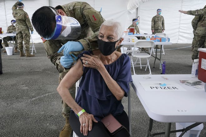 Ivonne Burgess, 81, gets the first dose of the Pfizer COVID-19 vaccine at a FEMA vaccination site at Miami-Dade College, Wednesday, March 3, 2021, in North Miami, Fla. This is one of four FEMA sites in Florida that opened Wednesday with capacity to vaccinate up to 3,000 people a day, seven days a week. (AP Photo/Marta Lavandier)