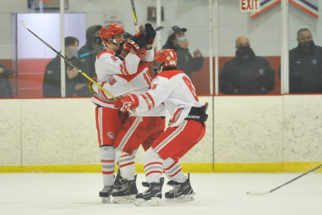 Cranston Co-Op's Kaden Santurri (left) gets mobbed by Joseph Rapoza and Ben Harding following his game-winning goal in overtime of the Falcons' 4-3 win in Game 1 of the Division II championship series against North Kingstown.