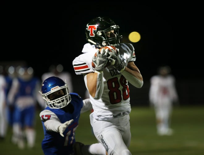 Thurston's Jacob Newell, right, pulls down a reception ahead of Churchill's Danny Womack during a game last season.