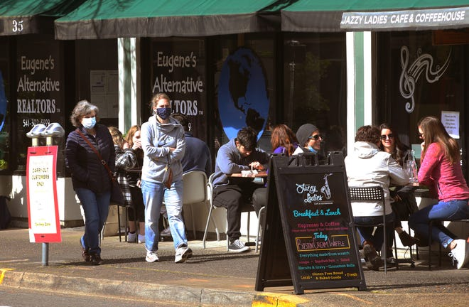 People grab lunch at outdoor seating along East Eighth Avenue in Eugene. The state put Lane County in a warning period, signaling the county may move to a higher risk level if it does not drive down COVID-19 case numbers.
