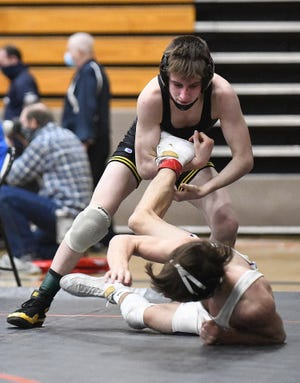 Austin McBurney of Perry has control of the leg of Ethan Smith of Jackson at the Division 1 Districts held at Hoover High School.
