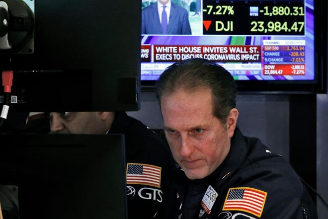 Specialist Glenn Carell, right, works on the floor of the New York Stock Exchange on March 9, 2020. Stocks went into a steep slide at the opening bell on Wall Street as coronavirus fears and a crash in oil prices spread alarm through the market, triggering the first automatic trading halt in over two decades.
