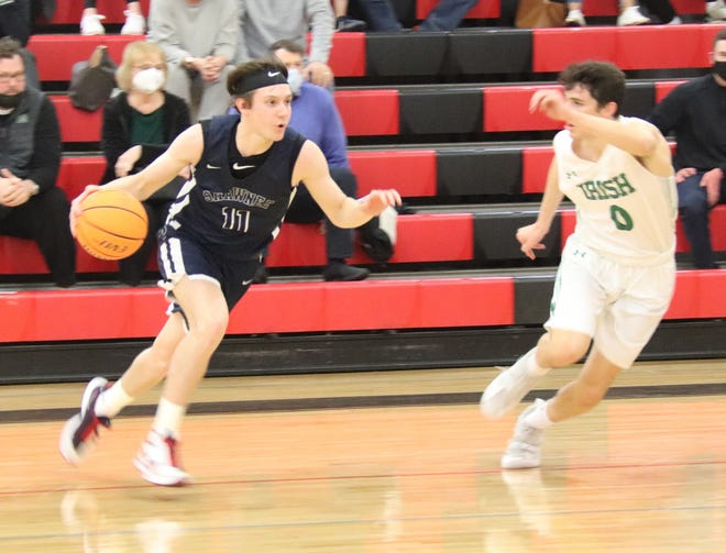 Shawnee junior guard Tanner Morris (left) prepares to drive the basketball past Bishop McGuinness' Luke Chansolme Friday night in Class 5A area play.