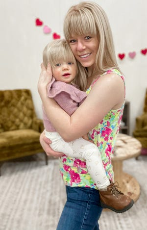 Lorin LaMarr of Fort Jones holds her 17-month-old daughter Everly at the Copper Mountain Boutique LLC on Miner Street in Yreka. (March 5, 2021)
