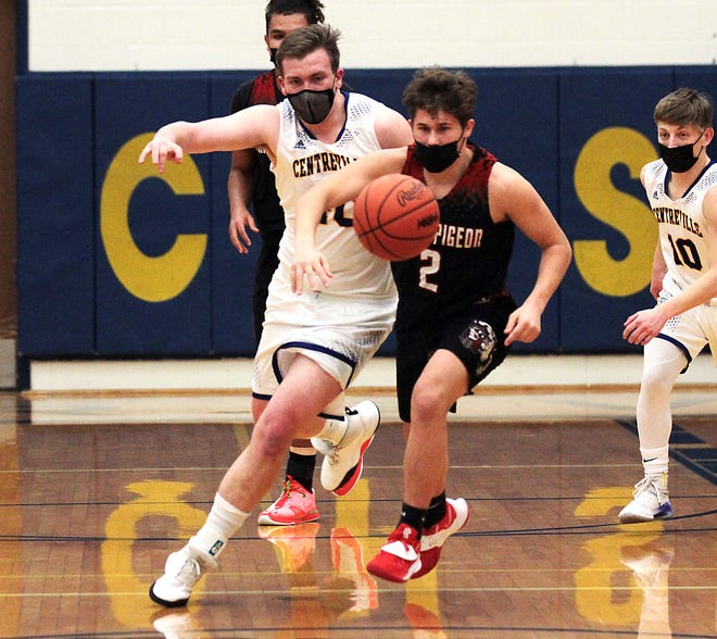Kody Beachey of Centreville and Dylan Carper of White Pigeon battle for a loose ball on Friday night.