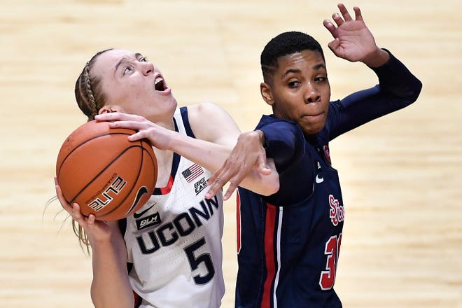 Connecticut's Paige Bueckers, left, looks to shoot while pressured by St. John's Kadaja Bailey during  the quarterfinals of the Big East Conference tournament at Mohegan Sun Arena Saturday in Uncasville.