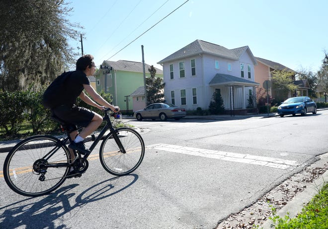 A cyclist rides past homes on Northwest Seventh Avenue and Northwest 10th Street in Gainesville on March 4.