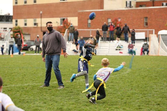Players compete in the Newton Area Flag Football League while a coach looks on.