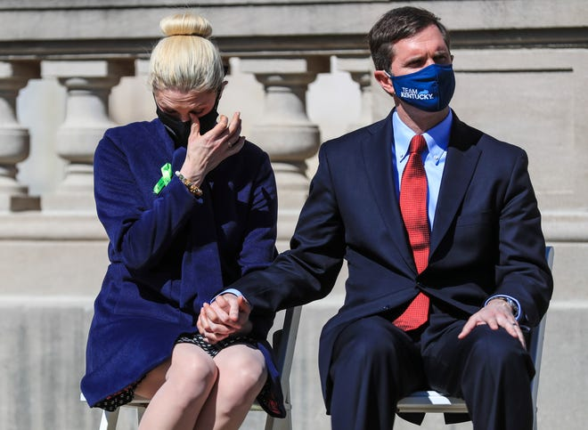 Kentucky first lady Britainy Beshear wipes away tears while holding her husband, Kentucky Gov. Andy Beshear, as they listen to family members who lost a loved one to COVID-19 during a memorial at the state Capitol in Frankfort on Saturday afternoon.