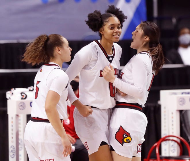 Louisville's Norika Konno (11), right, and Mykasa Robinson (5) celebrate with Ramani Parker (0) after Parker was fouled during the first half of Louisville's game against Syracuse in the semifinals of the ACC Women's Basketball Tournament in Greensboro, N.C., Saturday, March 6, 2021.