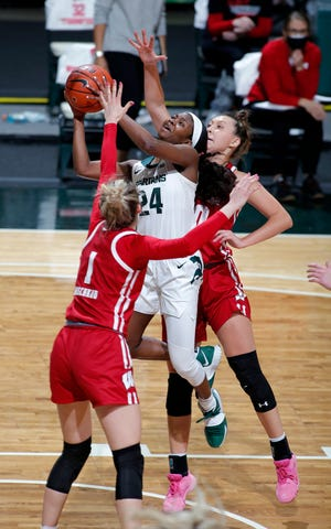 Michigan State's Nia Clouden (24) goes up for a shot against Wisconsin's Estella Moschkau, left, and Halle Douglass, Saturday, March 6, 2021, in East Lansing, Mich.
