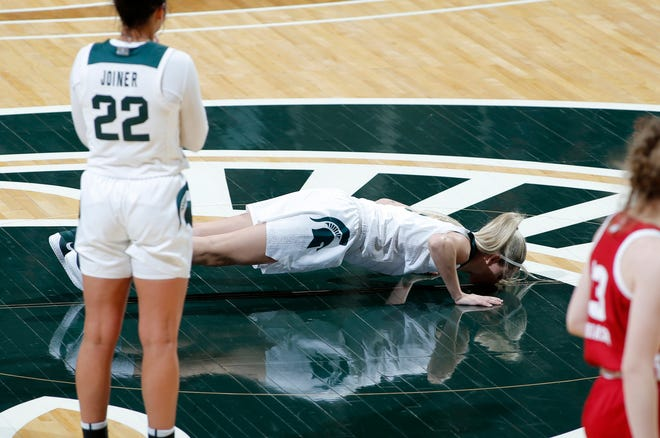 Michigan State senior Claire Hendrickson kisses the court as she comes out of the game against Wisconsin, Saturday, March 6, 2021, in East Lansing, Mich. MSU won 67-54.