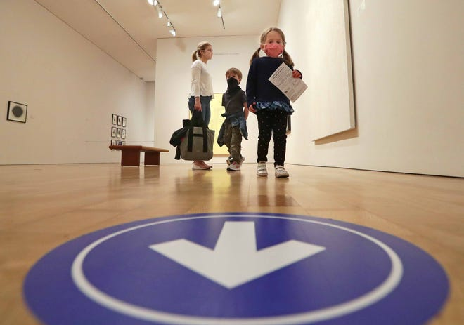 An arrow on the floor directs visitors Alexandra Megan, from left, son Graydon, 5, and daughter Madeline, 3, at the Milwaukee Art Museum on Saturday.