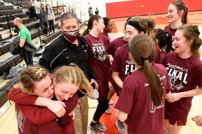 Newark girls celebrate with coach J.R. Shumate after their 75-73 victory against Dublin Coffman in a Division I regional final last Friday at Westerville South. Shumate served the first of a two-game suspension and couldn't enter the gym until after the game.
