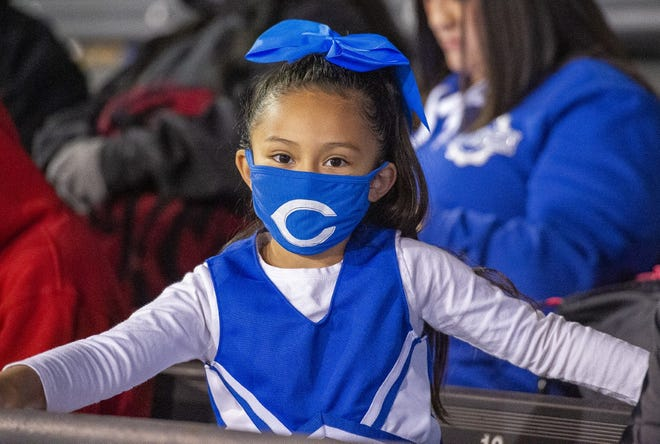 Masked and cheering for the Cavemen, this young fan was among 3,000 allowed to watch the Eddy County War on March 5 at the Watson Memorial Stadium in Hobbs, New Mexico.