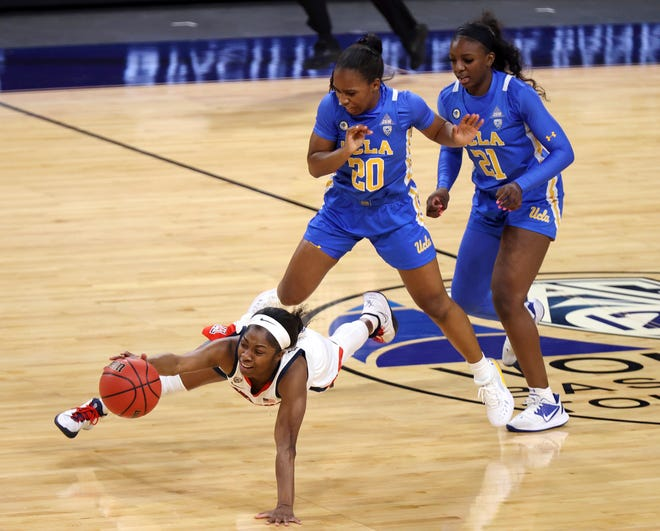 Arizona guard Aari McDonald (2) dives for a loose ball as UCLA guard Charisma Osborne (20) and forward Michaela Onyenwere (21) defend during the first half of an NCAA college basketball game in the semifinals of the Pac-12 women's tournament Friday, March 5, 2021, in Las Vegas. (AP Photo/Isaac Brekken)