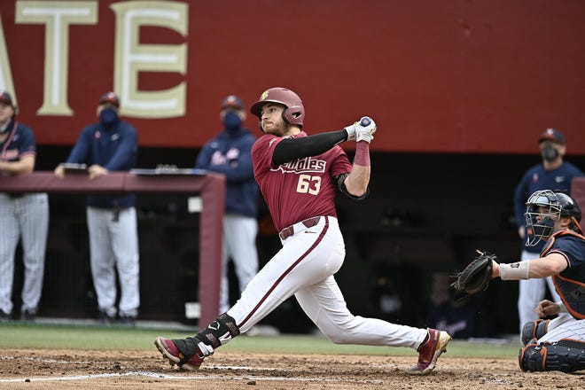 FSU catcher Matheu Nelson puts a ball in play during the Seminoles' game against Virginia on March 6, 2021.