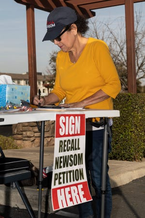 Lynda Baker signs a petition on Friday, March 5, 2021 in Visalia to recall California Governor Gavin Newsom. She said they and others have collected approximately 30,000 signatures.