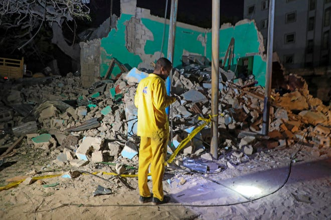 A man observes a destroyed building at the scene of a blast at a popular restaurant in the capital Mogadishu, Somalia Friday, March 5, 2021. A car packed with explosives rammed into a popular restaurant in Somalia's capital on Friday night, and police said at least 10 people were killed and more than 30 wounded.