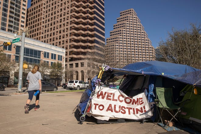 A woman walks past a homeless camp on West Cesar Chavez Street in Austin last month.