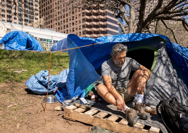 Al Perez sits in his tent at a homeless camp on West Cesar Chavez Street near the shore of Lady Bird Lake next to the Ann and Roy Butler Hike and Bike Trail on Friday March 5, 2021.