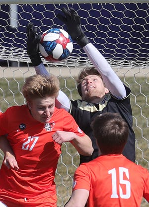 University of Akron goalkeeper Will Meyer makes a save in front of Bowling Green's Nathan Masters, left, and Kyle Cusimano during the Zips' 2-0 win Sunday in Akron. [Phil Masturzo/Beacon Journal]