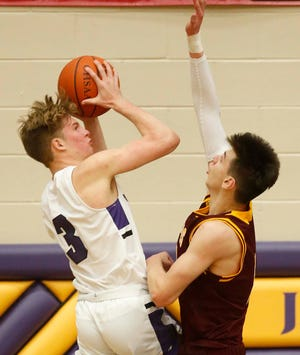 Kevin James, left, of Jackson goes up for two points over Erik Stern of Walsh Jesuit during the second half of their Division I District Final game at Jackson High School Saturday, March 6, 2021 in Jackson Township, Ohio.