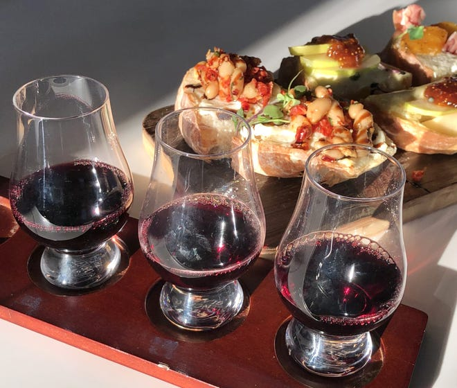 A flight of three California red wines is paired with a crostini board from Vinifera Wine & Whiskey Bar in Cuyahoga Falls.