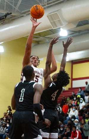 Corey Trotter of Cross Creek attempts a shot over D'ante Bass, left, and Abasi Scott, right, of Windsor Forest defenders at the boys high school basketball playoff game between Cross Creek and Windsor Forest on March 6, 2021 in Augusta, Ga. [MIKE ADAMS FOR THE AUGUSTA CHRONICLE]
