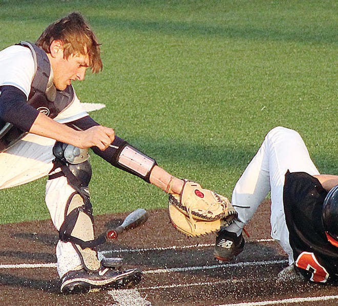 Bartlesville High starting catcher Silas Earley makes an ankle tag during a key play in Friday's varsity home battle against Tahlequah High. The umpire called the runner out. It turned out to an crucial decision because Bartlesville won in extra innings, 6-5.