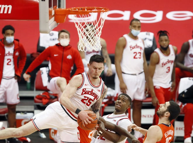 Ohio State Buckeyes forward Kyle Young (25) comes down with rebound against Illinois Fighting Illini guard Da'Monte Williams (20) during the second half of their game at Value City Arena in Columbus, Ohio on March 6, 2021.