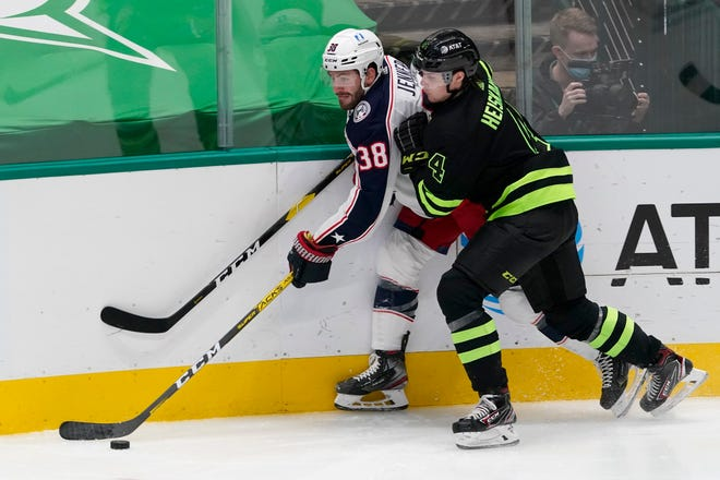 Boone Jenner (38) attempts to make a pass under pressure from Stars defenseman Miro Heiskanen (4) in the second period Saturday night at American Airlines Center in Dallas.