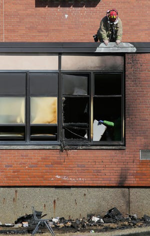 Firefighters from Columbus Divison of Fire's Station 22 investigate after extinguising a fire at Buckeye Middle School on Parsons A\ve on the south side of Columbus on Sunday, March 7, 2021.