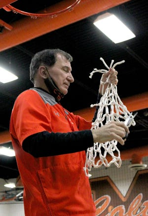 Meadowbrook head coach Lou 'Scooter' Tolzda takes a turn cutting down the net after the Colts' 45-26 victory over Cambridge to win the Division II district championship on Saturday at Meadowbrook High School. Tolzda recently was named the Division II Coach of the Year in by the District 12 Basketball CoachesAssociation.