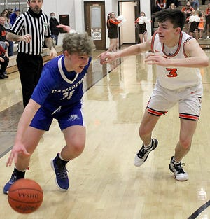 Cambridge freshman Colton Slaughter (11) attempts to drive past Meadowbrook junior Jake Singleton (3) during Saturday's Division II district championship game at Meadowbrook High School. The Colts claimed the district title and a return trip to the regionals with a 45-26 victory.