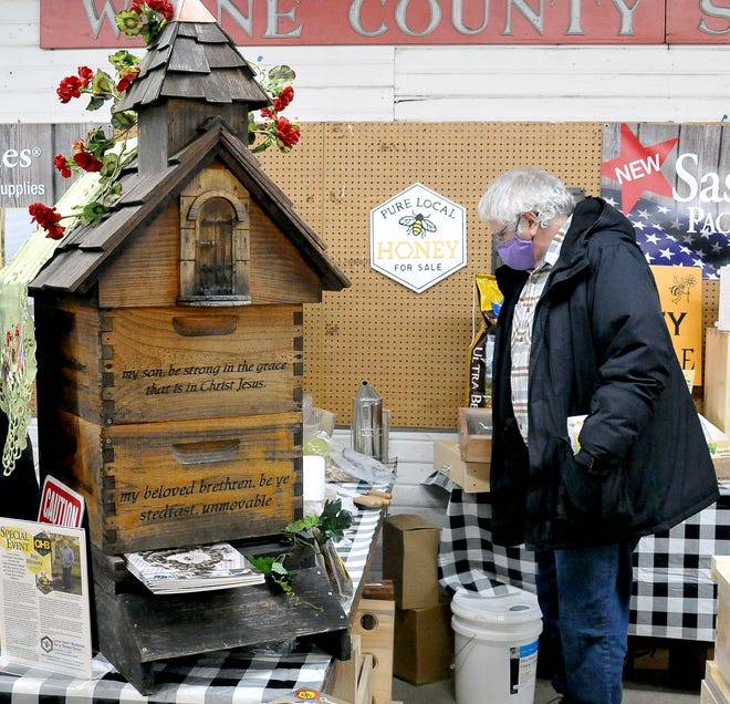 Richard Moore, a Hilliard resident who has bees located in Wayne County, checks out items near a one-of-a-kind beehive.