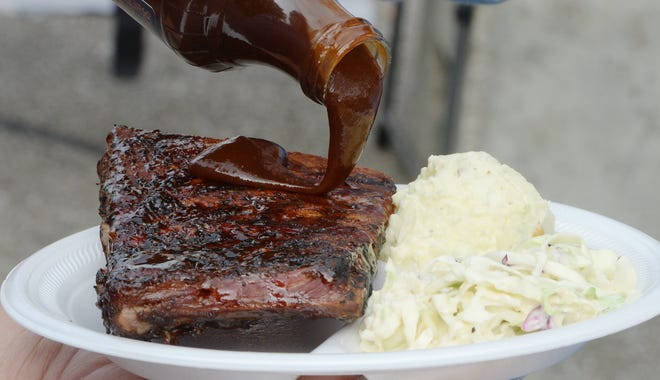 Diners pour sauce on ribs from Underdog BBQ during Erie's Wild Rib Cook Off & Music Festival on May 29, 2019. The first Cook Off since then is now scheduled to take place Sept. 15-18 in Perry Square.