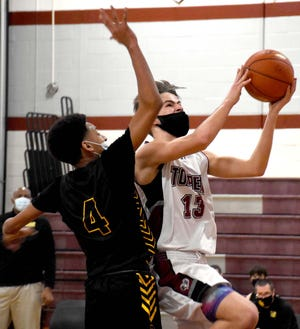 Levi Thomas goes up for a layup for Fort Plain with Canajoharie Cougar LA Fairley (4) defending Saturday, March 6, 2021, during the first half of a game played in Fort Plain, New York.