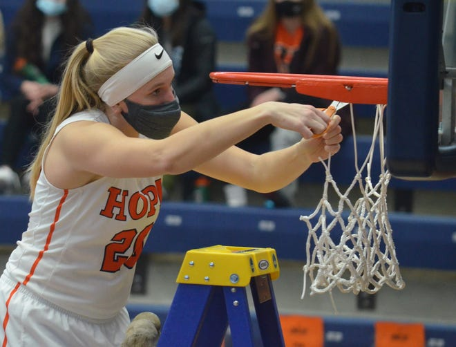 Hope's Kenedy Schoonveld cuts down the net at DeVos Fieldhouse after Hope won the MIAA title on Saturday.
